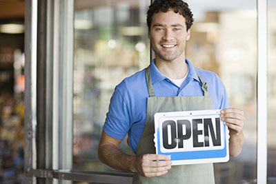 image of small business owner holding an open sign
